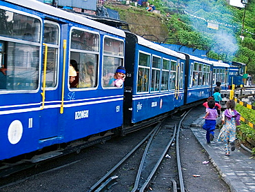 kids chasing the toy train as it leaves the station in Darjeeling