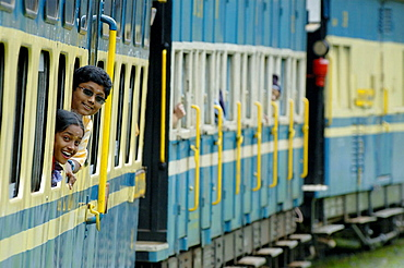 Loughing girls looking out of the train windows of the Nilgiri Mountain Railway driving from Coonoor to Ooty, Tamil Nadu, India 2005