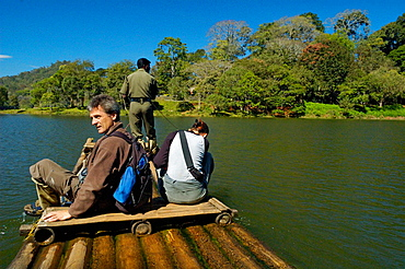 Two western tourists in the Periyar Tiger Reserve crossing the Periyar Lake by raft with their local Indian guide, Periyar (Kumily), Kerala, India 2005