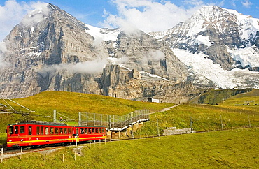 Jungfraubahn train with the Eiger and Monch mountains and the Eigergletscher glacier, Bernese Oberland, Switzerland