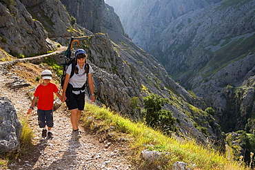 Family of hikers walking along the route of the Cares Canyon, in the Picos de Europa National Park, between the Urrieles and andara massifs, Poncebos, Cantabria, Spain