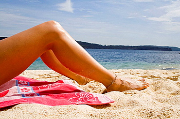 Legs of a woman sunbathing on a beach, Sydney, Australia
