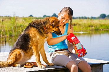 Teenaged girl and her pet dog eating potato chips outdoors at a lake