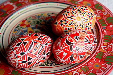 Three red traditional Czech Easter eggs on a handpainted wooden Bohemian plate