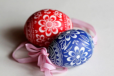Two traditional red and blue handpainted Czech Easter eggs with ribbons