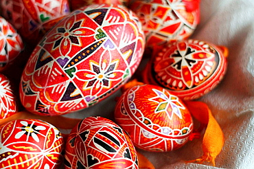 A half basket of  red hand-painted Czech Easter eggs.