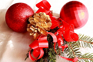 Two red Christmas balls with red ribbon and yew on white linen Two red Christmas balls with red ribbon and yew on white linen Two crimson balls with a gilt pine cone with yew are on white damask linen