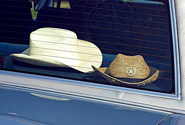 horizontal, car, glass, vehicle, behind, sunhats, sunhat, male, cowboy, nobody, headwear, couple, pair, hats, rear window, americana, objects, things, nobody, straw hat, sun hat, journey, trip, travel, vacation, kitsch, outfit, accessories