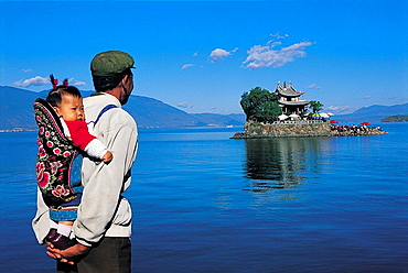 Bai man and child watching the temple and island of xiao putuo dao, erhai lake, yunnan, China