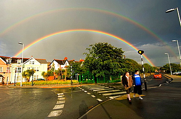 Two men walking across a zebra crossing with a dark cloudy sky with double rainbows over Aberystwyth town, Ceredigion, West Wales, May 2007