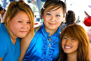 Three teen girls SE Asian Hmong enjoying the cultural festivities Hmong Sports Festival McMurray Field St Paul Minnesota USA