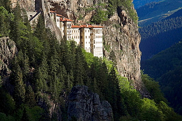 TURKEY, Trabzon, Sumela Monastery - Greek Orthodox Monastery of the Virgin Mary - clinging to a sheer rock wall above evergreen forest