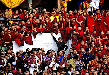 Monks and novices at a Bhutanese dzong, or monastery, watch the dancers at the Tsechu, an annual three day Tibetan Festival, Bhutan