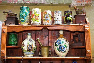 Antique pottery items for sale on shelving outside an antique shop, Sighisoara, Transylvania, Romania