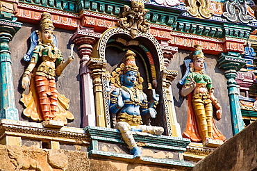 Three carved figures on a gopuram, Meenakshi Temple, Madurai, Tamil Nadu, India