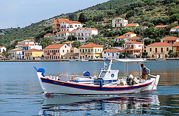 Boat moving in harbour and Vathi town behind, Vathi, Ithaca, Greece