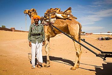 Man standing beside a camel, Osian Camel Camp, Osian, Rajasthan, India