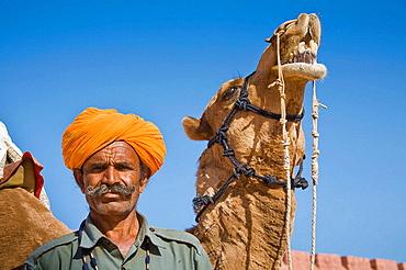 Man standing beside a camel at Osian Camel Camp, Osian, Rajasthan, India