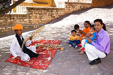 Young man playing a ravan hatta musical instrument, at Mehrangarh Fort, Jodhpur, Rajasthan, India