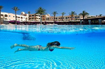 Girl in swimming pool in luxury hotel.