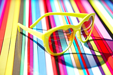 Heart shaped sunglasses on a multi coloured stripey background