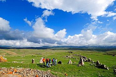 tourist group at Zorats Karer, 6000 B.C, stoneage observatory, menhir of Karahunj, Cara Hunge, Armenia, Asia
