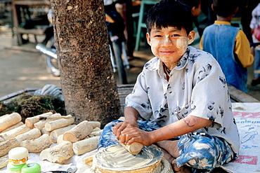 Myanmar, Mingun, boy making tanaka makeup paste
