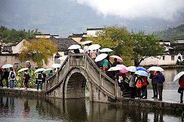 China, Anhui Province, Hongcun village, bridge, people with umbrellas