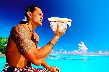 Tattoed young man blowing in a seashell, Bora Bora, Leeward Islands, French Polynesia