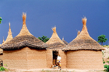 Woman entering in a podoko compound of adobe cabins and millet straw roofs, Mounts Mandara, Cameroon