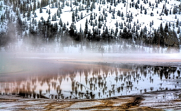 The nearby landscape is reflected on Grand prismatic Springs runoff during winter at Yellowstone National Park, Wyoming