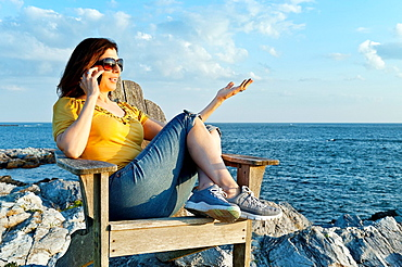 Woman enjoys the coastal view while speaking on a mobile phone