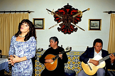Fado singer and guitarists in a night club, Lisbon, Portugal