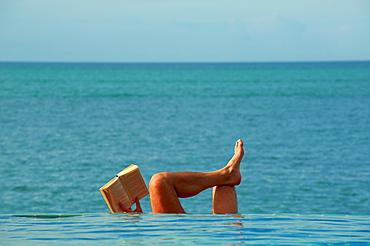 Thailand, Siam gulf, Ko Samui island, man reading book at the swimming pool