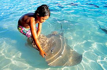 Young boy with stingray, Bora Bora, Leeward Islands, French Polynesia