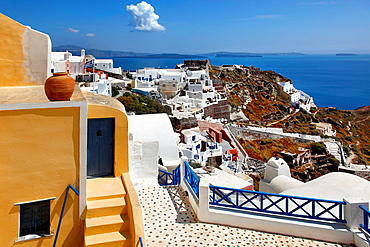 Yellow home with blue fencing and deck overlooking hillside and caldera in the village of Oia in Santorini, Greece