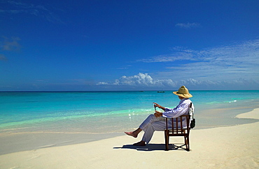 Guest on his lap top on the beach, Mnemba Island, Zanzibar