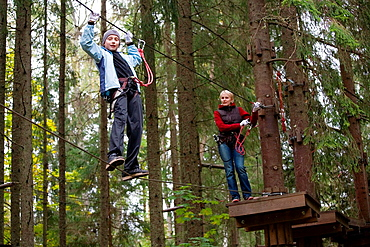 Young woman and teenage boy on zip wire in adventure park trail in Otepää, Estonia