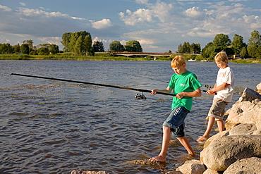 Two Teenage Boys Fishing on Pier by Lake Võrtsjärv in Estonia
