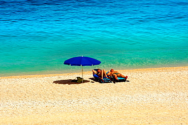 Couple sunbathing on the famous Turquoise waters of Myrtos Beach aaa t, Kefalonia, Greek Ionian Islands