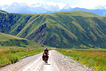 Male cyclist on a mountain road, Kyrgyzstan Naryn-Too Range seen in the background