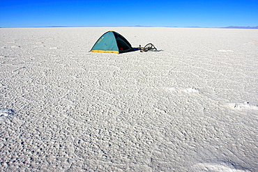 A tent and a bicycle on the frozen salt lake called Salar de Uyuni in Bolivia