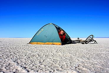 A biker in a tent on the frozen salt lake called Salar de Uyuni in Bolivia