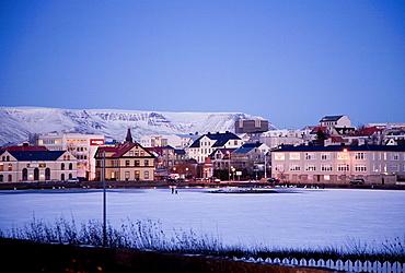 Two persons walking on a frozen Tjornin lake Downtown Reykjavik, Iceland