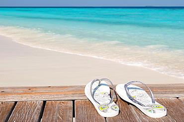 Flip flops on a jetty next to a white sand beach Maldives