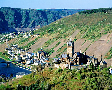 Germany, Cochem, Moselle, Moselle valley, Rhineland-Palatinate, panoramic view, Moselle landscape, vineyards, mountain range of the Eifel, Reichsburg Cochem, imperial castle, Gothic Revival, in the background church Saint Remaclus, catholic church. Germany, Cochem, Moselle, Moselle valley, Rhineland-Palatinate, panoramic view, Moselle landscape, vineyards, mountain range of the Eifel, Reichsburg Cochem, imperial castle, Gothic Revival, in the background church Saint Remaclus, catholic church