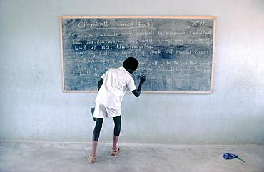 Nigerian schoolboy writing on chalk blackboard in classroom during geology lesson Nigeria