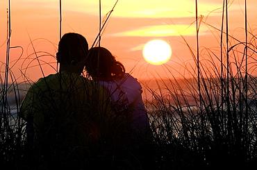 Young Couple Watching Sunset, Sanibel Island, Florida USA