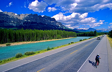 Cyclist along Highway One, Castle Mountain and the Bow River beyond, Alberta, Canada
