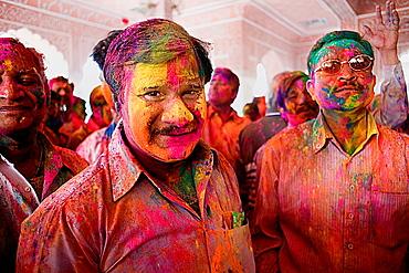 Friends celebrating the Holi spring festival to celebrate the love between Krishna and Radha, in Govind Devji temple, Jaipur, Rajasthan, India